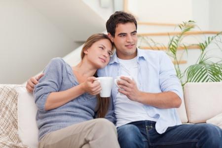 Прекрасная пара смотрит телевизор, попивая кофе в гостиной ...